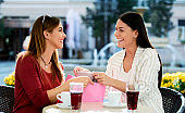 Two women relaxing after shopping in a cafe. Consumerism, lifestyle concept