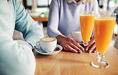 Young couple sitting in the cafe, drinking coffee and juice, close up photo. Dating, love, relationships