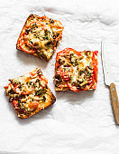 Delicious breakfast. Hot sandwiches with mushrooms, tomatoes, mozzarella, thyme on a light background, top view