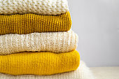 Pile of knitted clothes yellow white color. Autumn winter concept.