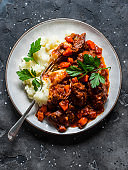 Classic beef stew with mashed potatoes on a dark background, top view. Delicious comfort homemade food