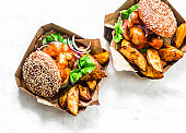 Tomato sauce meatballs mozzarella cheese whole grain buns burgers and baked potatoes on a light background, top view