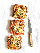 Hot sandwiches with mushrooms, tomatoes, mozzarella, thyme on a light background, top view. Delicious appetizer, snack, tapas