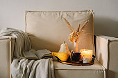 Still life details in home interior of living room. Pumpkin and cup of tea with candles on a serving tray