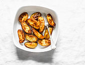 Baked new potatoes in baking dish on a light background, top view. Delicious snack, tapas