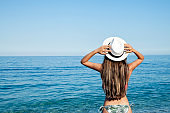 Beach vacation. Hot beautiful woman in sun hat and bikini standing with her arms raised to her head enjoying looking view of beach ocean on hot summer day.
