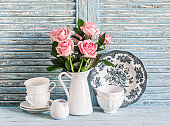 Vintage white crockery and rose bouquet on blue wooden background. Kitchen still life in vintage english country style. Flat lay