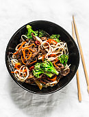 Udon noodles with beef and vegetables - delicious lunch on a light background, top view. Balanced food