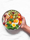 Women hand with a large snack plate. Boiled egg, broccoli, carrots, apples with peanut butter, grapes - delicious diet breakfast, snack on a light background, top view
