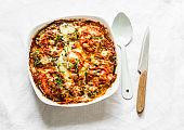 Eggplant, chicken, tomatoes, mozzarella cheese, tomato sauce casserole on a light background, top view
