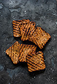 Whole grain seeds grilled toast bread for sandwiches on a dark background, top view