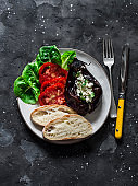 Greek style baked eggplant with feta cheese, tomatoes, green salad, homemade bread - delicious appetizer, tapas, snack on a light background, top view