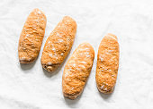 Homemade whole grain hot dogs buns on a light background, top view