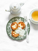 Breakfast served table - cottage cheese pancakes with sour cream, green tea on a light background, top view
