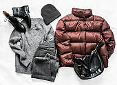 Women's winter autumn clothing - down jacket, jeans, hat, sweater and boots on a light background, top view. Fashion concept