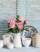 Vintage crockery in english style and rose bouquet on blue wooden rustic background. Kitchen still life in vintage country style. Flat lay