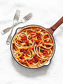 Traditional italian roman pasta - bucatini with amatricana tomato sauce in a cooking pan on a light background, top view