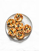 Minced meat, spinach, mozzarella cheese mini hand pies for appetizers, tapas, snack on a light background, top view