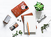 Women's table with notebooks, cosmetic, pens, succulent flower on a light table, top view. Flat lay beautiful female still life