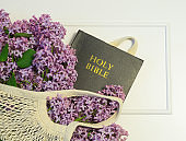 Blooming spring lilac flowers in string bag with bible