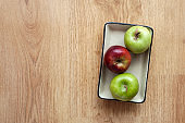 Ceramic plate in apples on wooden background.