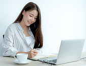 Young woman student taking notes watching laptop study online class video conference education elearning course from home