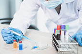 Doctor hold the pipette and drop the blue chemical liquid into a petri dish for research and analysis for treating viral and bacterial illness in a laboratory