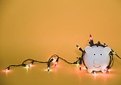 White piggy bank with Christmas string lights on happy December festival, Enjoy savings for spending money on the holiday's concept