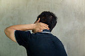 Man holding his neck in pain on grey background.