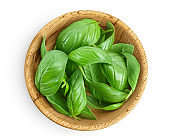 Fresh basil leaf in wooden bowl isolated on white background with clipping path and full depth of field. Top view. Flat lay