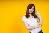 Close up of young Asian woman isolated on yellow background showing thumps up with positive emotions of content and happiness. Copyspace, concept of satisfaction with quality and recommendation.