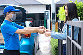 Asian delivery man delivering food, fruit, joice and vegetable to customer home - online grocery shopping service concept