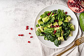 Salad with pomegranate, avocados, spinach on white background top view flat lay