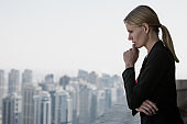 Executive woman thinking at work while looking at the city view from a high-rise. Business career challenges.
