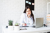 Young sad brunette teacher writing having online class