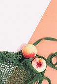 Fresh peaches in a mesh bag or string bag.  Zero waste. Eco life concept.  Flat lay. Minimal