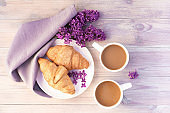 Two beautiful porcelain cups of coffee with milk with croissants decorated with lilac flowers on white wooden table. Perfect breakfast concept. Top view.