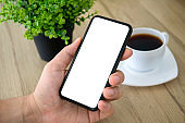 male hand holding phone isolated screen over table in cafe