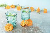 Two beautiful vintage turquoise glasses with cold drink and ice cubes, with fresh green mint leaves decorated with marigold flowers on natural colorful stone table.