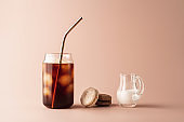 Glass of iced coffee in tall glass with golden straw with cream and macaroons chocolate, vanilla on pastel background for your design. Food concept in vintage style.