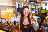 Beautiful smiling female Bartender serving a draft beer at the bar counter , shelves full of bottles with alcohol on the background