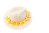 Straw hat with with yellow lily flowers on isolated white background. Stylish retro design template. Summer fashion concept. Copy space.