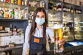 Beautiful female Bartender wearing protective face mask, serving a draft beer during coronavirus pandemic, shelves full of bottles with alcohol on the background