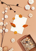 Autumn background with fall winter decor, blank stationary template, invitation mock up, empty paper card with copy space for text from top on beige background. Top view. Flat lay. Fall winter seasons