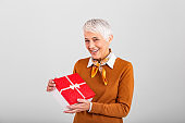 Cheerful good looking senior woman holding a red Christmas gift box in her hands, against a gray background. Concept holidays and presents