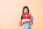 Portrait of a happy smiling girl opening a Christmas gift box isolated over yellow background. Excited young casual brunette woman holding present box