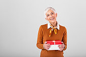 Portrait of cheerful positive glad charming aged woman with hairstyle having Christmas gift box in red package with white bow enjoying holiday festive mood isolated on grey background