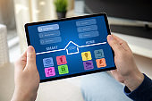 man hands holding computer tablet with app smart home