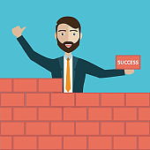 Successful businessman in yellow hard hat with trowel and bricks building a new business, for start-up theme design.
