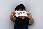 HELP, Teenager with help sign. Boy holding a paper with the inscription. Kid holding sheet of paper with word HELP on grey wall background.